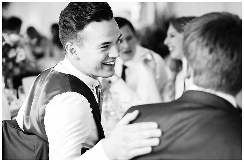 laughing best man places hand on grooms shoulder during Oxfordshire friars Court Wedding