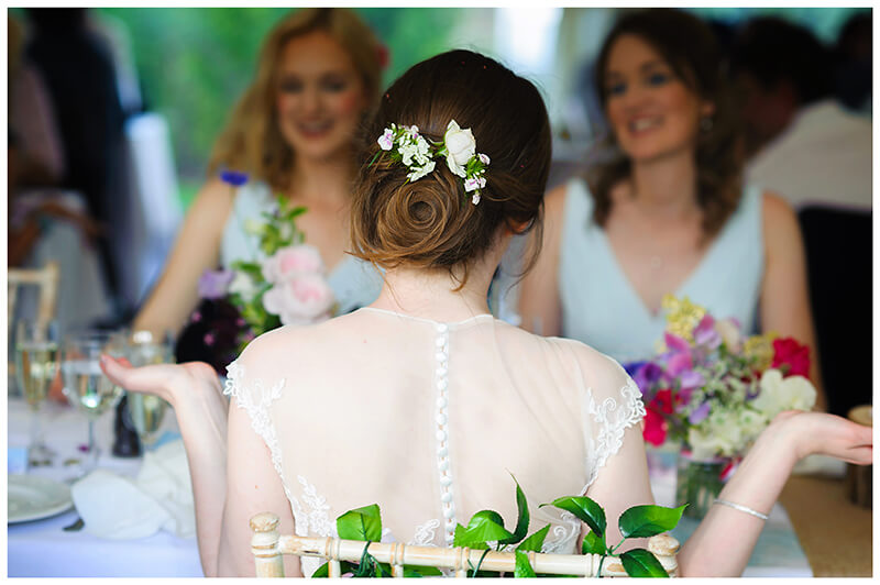 bride with hands wide showing flowers in hair