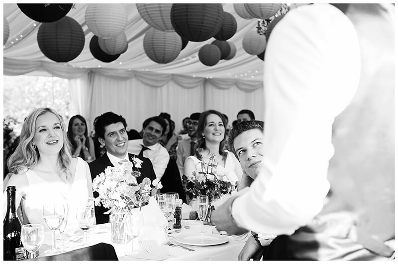 groom watches bestman during his speech bridesmaid laughs