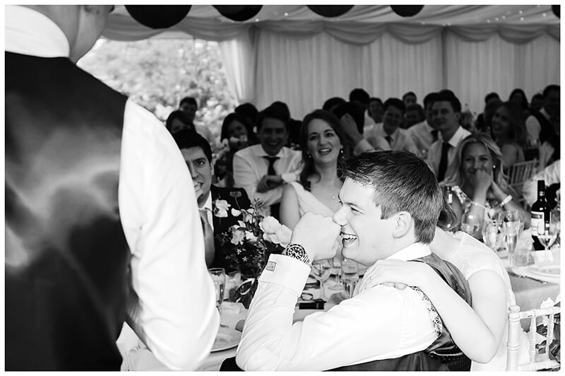 Oxfordshire friars Court Wedding bride places reassuring hand on grooms shoulder during speeches