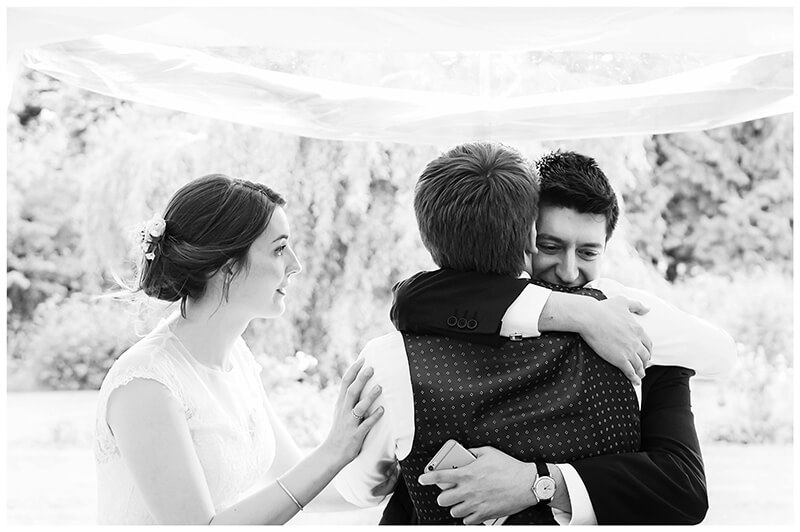 bestman hugs groom bride touches grooms shoulder