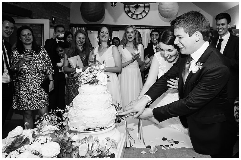 Wedding cake cutting by bride and groom
