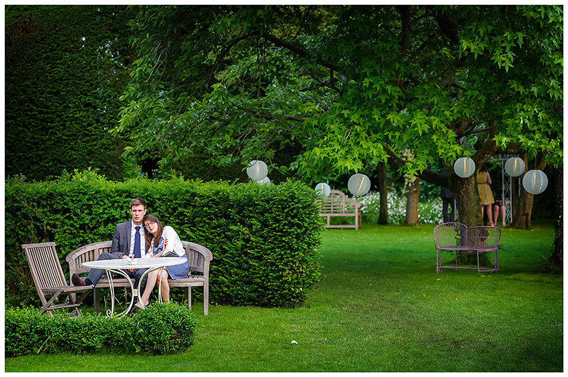 Wedding couple cuddle sitting on bench in gardens of friars Court