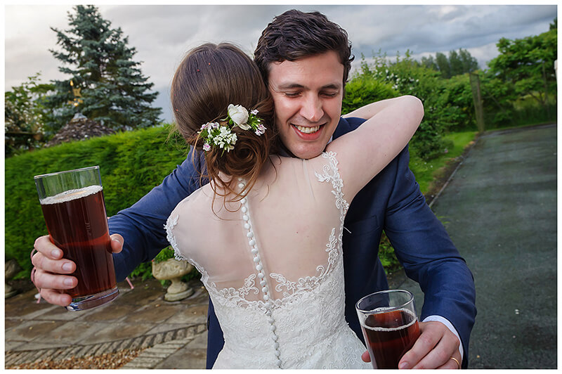 friars Court Wedding bride hugs guy carrying two pints of beer