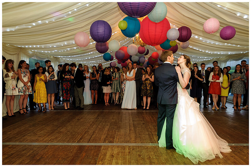 bride groom during first dance under colourful lanterns in marquee atched by guests