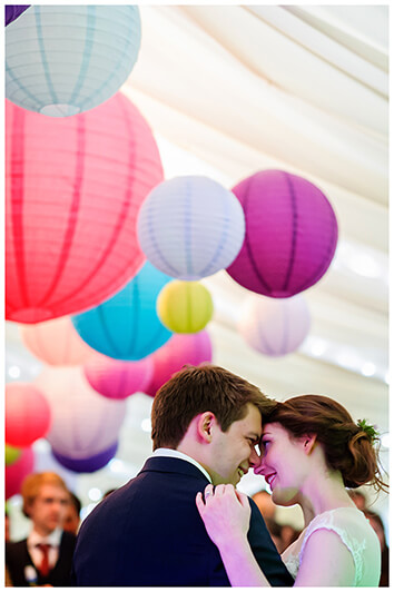 bride groom touch heads during first dance colourful lanterns above them