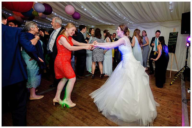 bride dancing with female guest in red dress