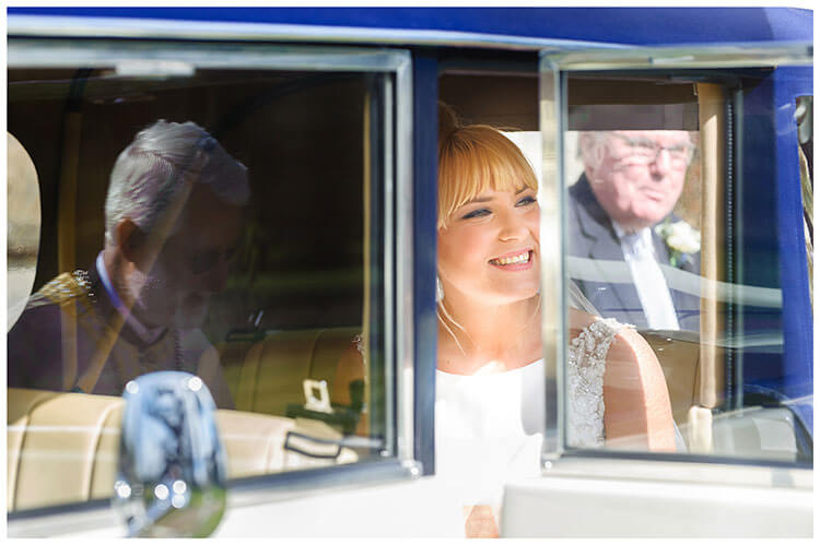 Royal Chapel Windsor Great Park smiling bride in car reflections and framing