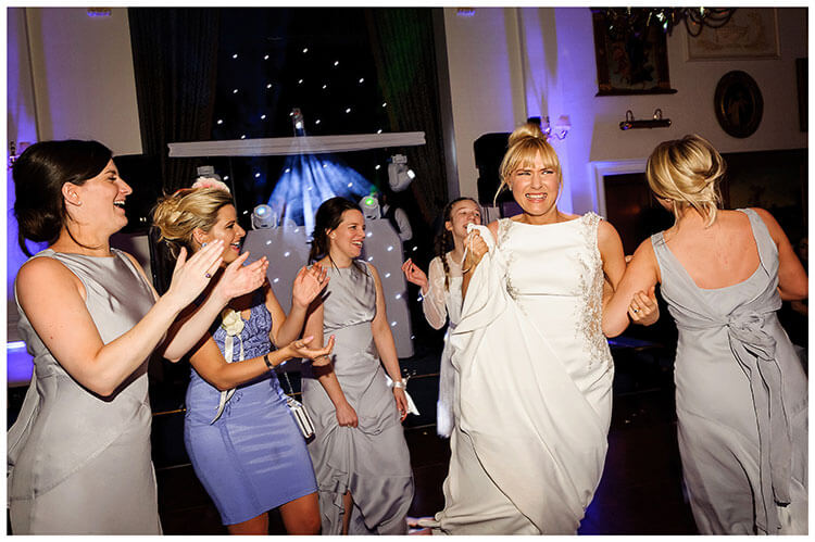 Wentworth Club Surrey Bride smiling while dancing with bridesmaids