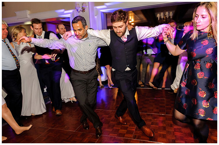 Wentworth Club Surrey groom and guests arm in arm doing Greek dancing