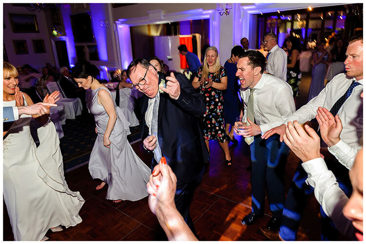 Wentworth Club Surrey dad playing an imaginary guitar on the dance floor guests cheering him on