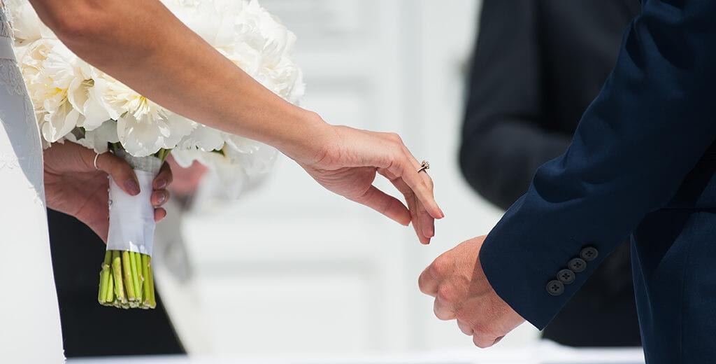 Destination wedding photography Mykonos wedding Bride places hand into grooms hand