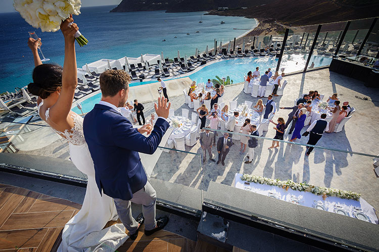 Destination wedding photography in Mykonos Bride groom standing on balcony waving at guests