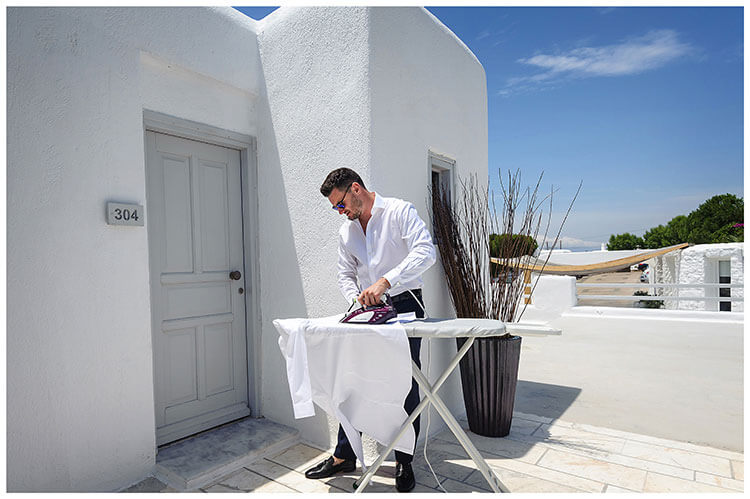 Bestman doing some ironing outside under a blue sky destination wedding in Mykonos at the Andronikos hotel
