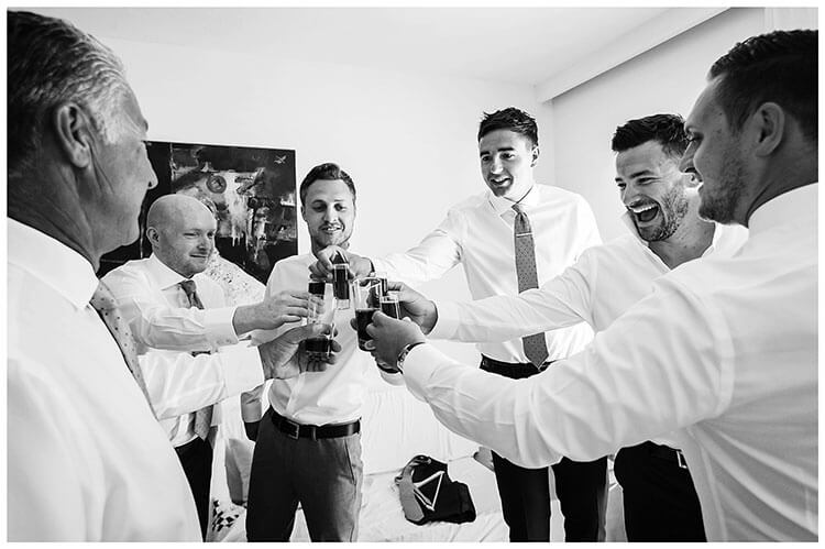 groom and usher enjoy a drink before leaving for ceremony Mykonos destination wedding
