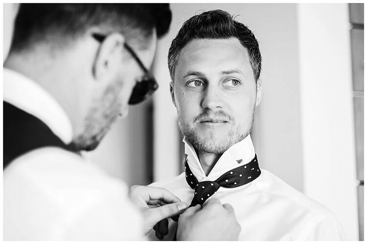 Groom has his tie done up by bestman destination wedding in Mykonos at Andronikos hotel