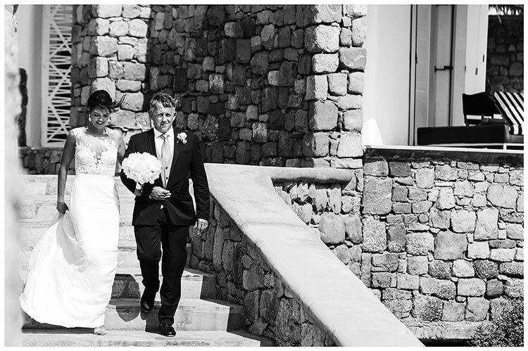 Bride on fathers arm walking down steps for wedding ceremony in Mykonos at the Andronikos hotel