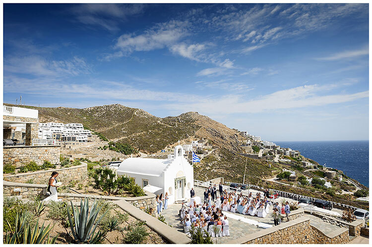 Bride walking down steps with father Chapel and guests under a blue Greek sky Mykonos destination wedding