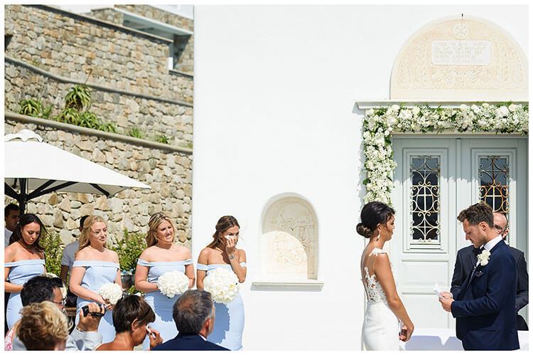 As Groom reads his vows a bridesmaid sheds a tear during destination wedding in Mykonos