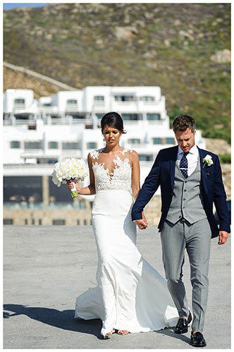 Bride & Groom holding hands walking along road with white washed Greek buildings in background Mykonos destination wedding