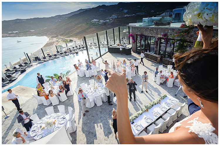Bride waves to guests from balcony overlooking Aegean Sea on Mykonos at Royal Myconian Resort Hotel