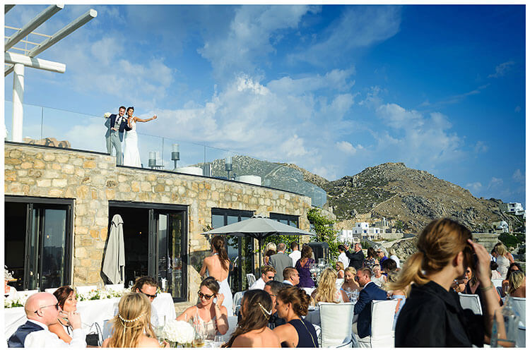 Bride & Groom waving to guests from balcony during wedding at Royal Myconian Resort Hotel Mykonos