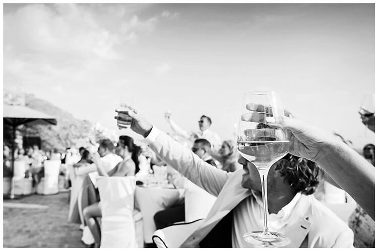 guests raise glasses of wine during Greek Island destination wedding