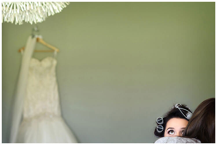 Best Wedding Photography of 2017 wedding dress hanging on wall during make up