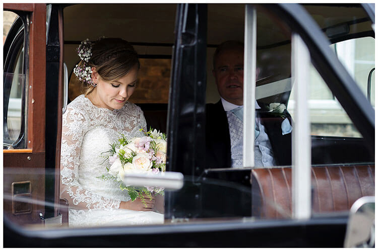 Best Wedding Photography of 2017 bride in car waiting looking at bouquet
