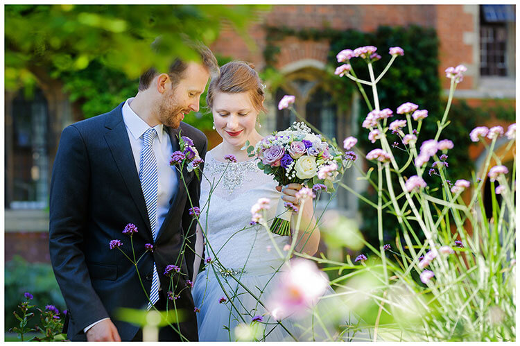 Best Wedding Photography of 2017 romantic moment as bride groom walk past purple flowers