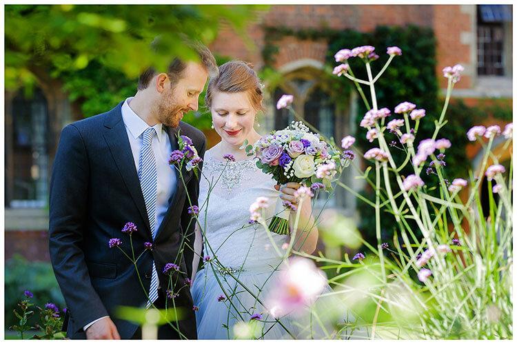 Best Wedding Photography of 2017 romantic moment as bride groom walk past purple flowers