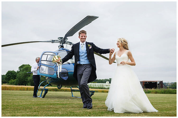 smiling Bride groom holding hands walking past helicopter