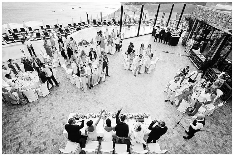 Best Wedding Photography of 2017 all the guests standing for a toast to the bride and groom over looking Mykonos sea