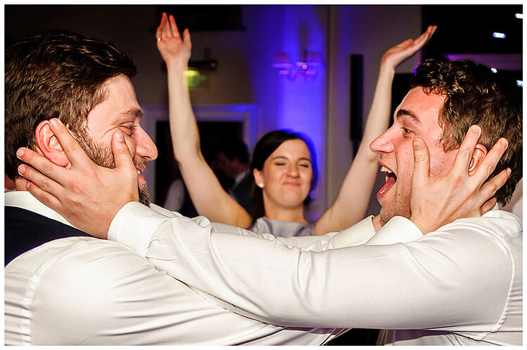 Best Wedding Photography of 2017 groom and male guest grasp each others faces in joy female in background smiling with arms in the air