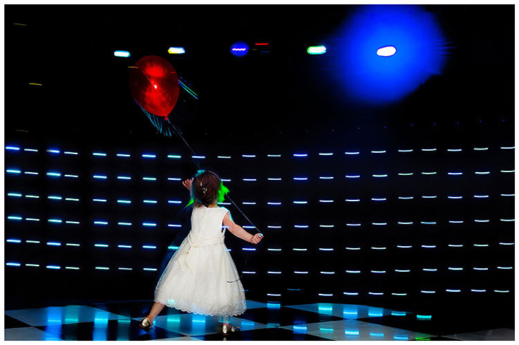 Best Wedding Photography of 2017 flowergirl with red balloon dancing in front of lights