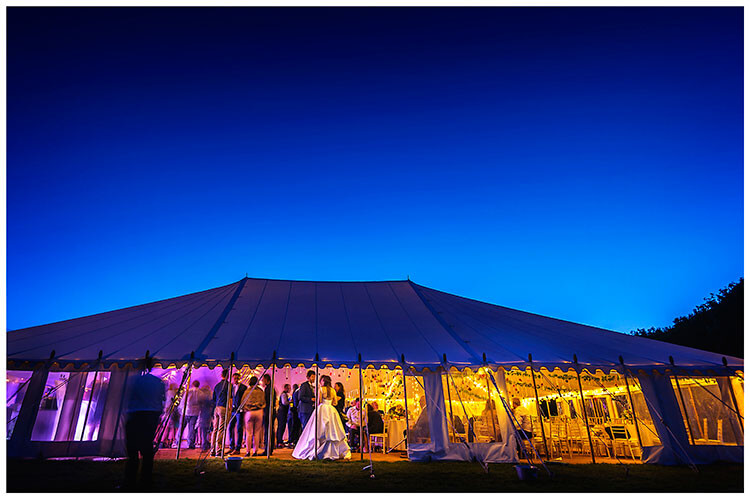Best Wedding Photography of 2017 bride standing talking to guests in marquee under deep blue evening sky