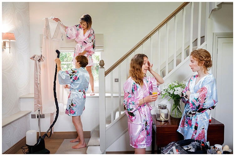 Bridesmaids talking while their dresses are steamed to remove creases