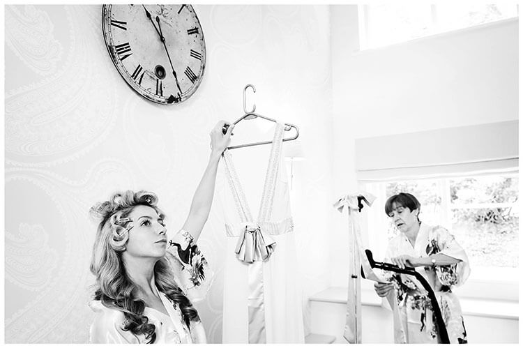 Bride standing under wall clock holds up bridesmaid dress while mother steamers another dress in background