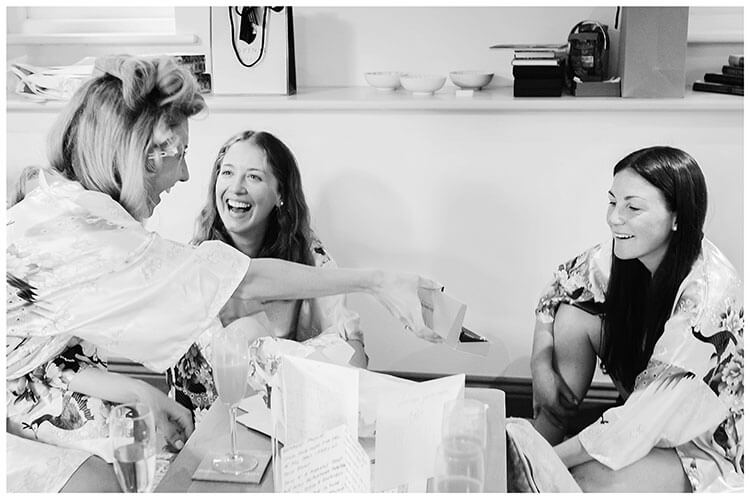 bride shows smiling bridesmaids present from future husband during her preparations