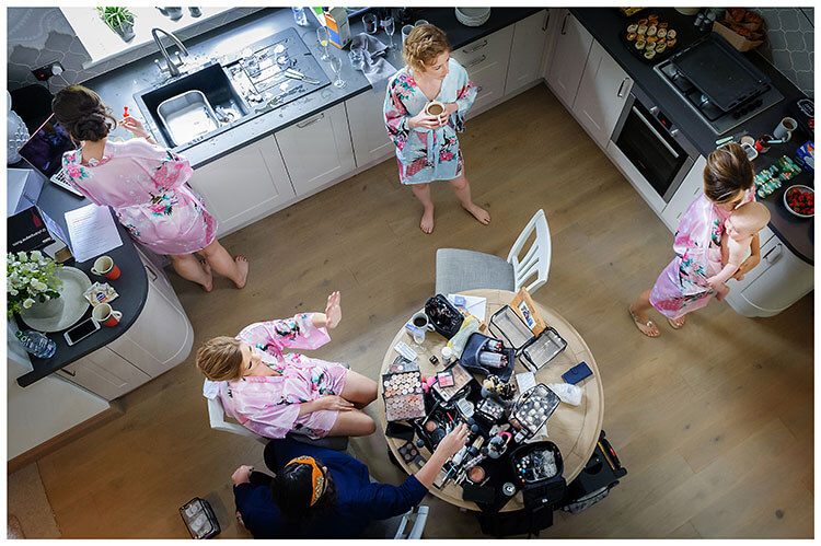 Bridesmaids dressed in pink and blue kymono's in kitchen having make up done