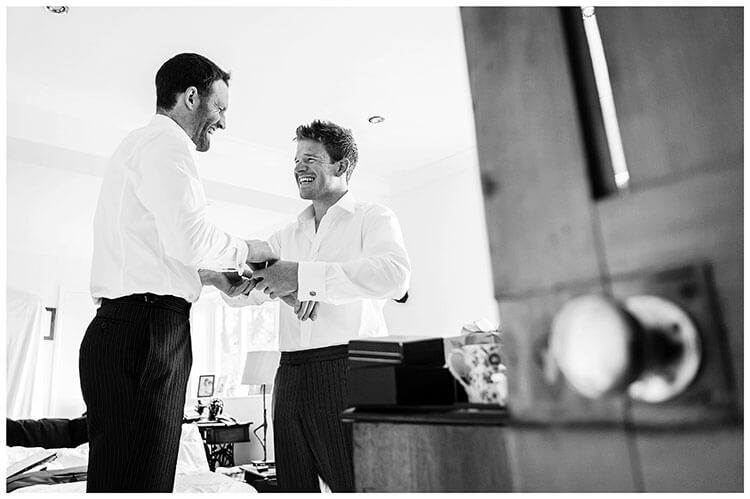 laughing groom getting help doing up cuff links
