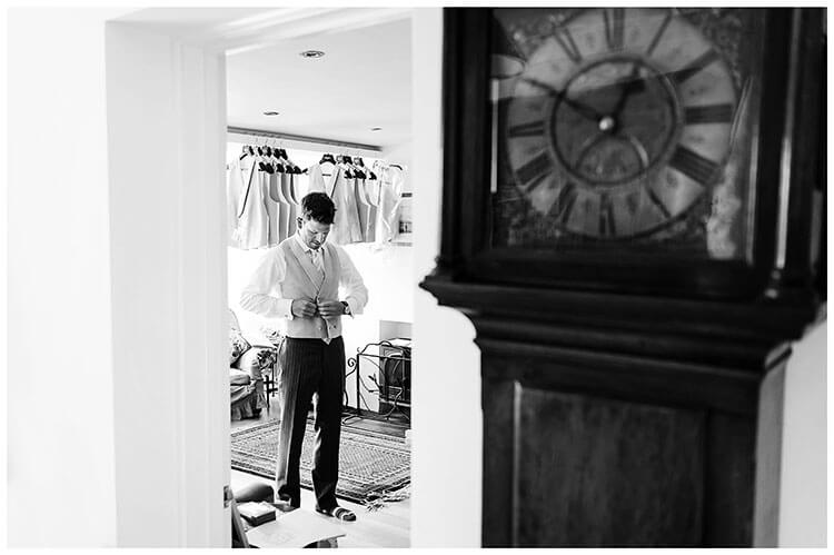 Groom doing up waistcoat grandfather clock in foreground