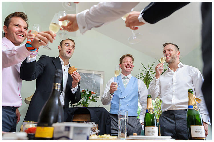 Groom and ushers enjoying a glass of champagne and something to eat before heading off for a village wedding