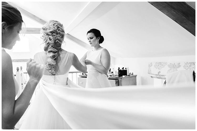 bridesmaids helping bride get ready long wedding dress waist band ribbons
