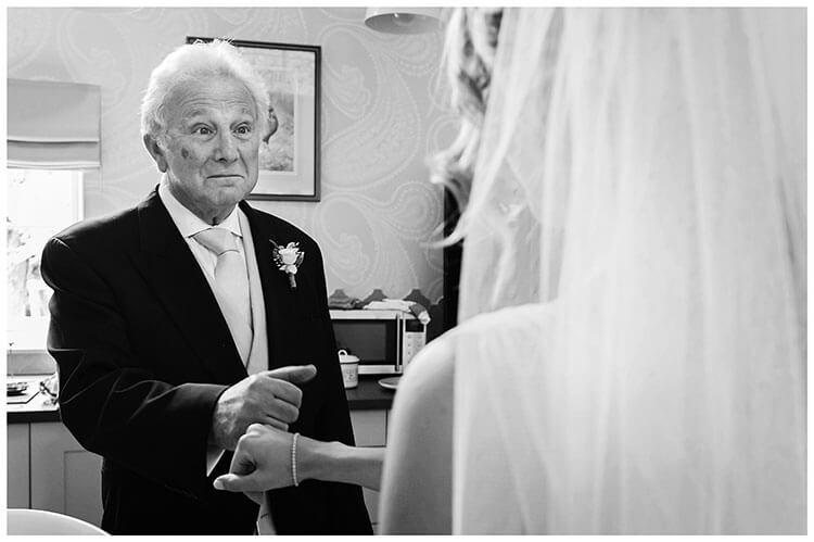 Cambridgeshire village wedding Brides Fathers first look bride and father touch hands