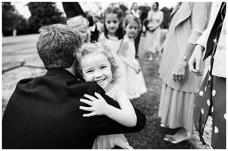Groom gets a hug from young Flowergirl