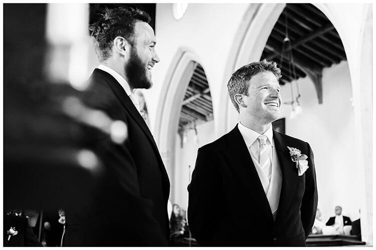 Cambridgeshire village wedding Groom and Bestman waiting inside Crishall Church