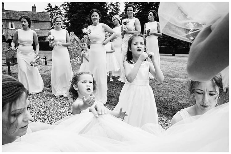 Crishall village wedding Bridesmaid watching as bride has dress tidied by bridesmaids