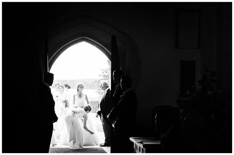 Bride and bridal party waititng to enter Crishall Church for Village wedding