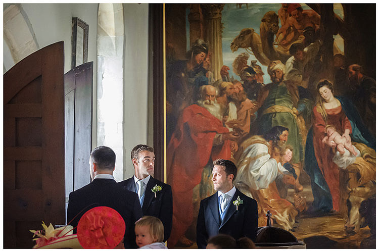 Village wedding at Crishall Church cambridgeshire Usher waiting in from of large painting for Bride to enter